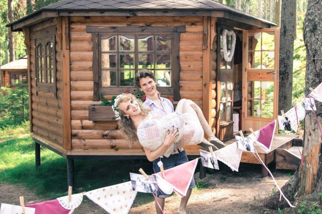Парень держит девушку на руках возле деревянного дома